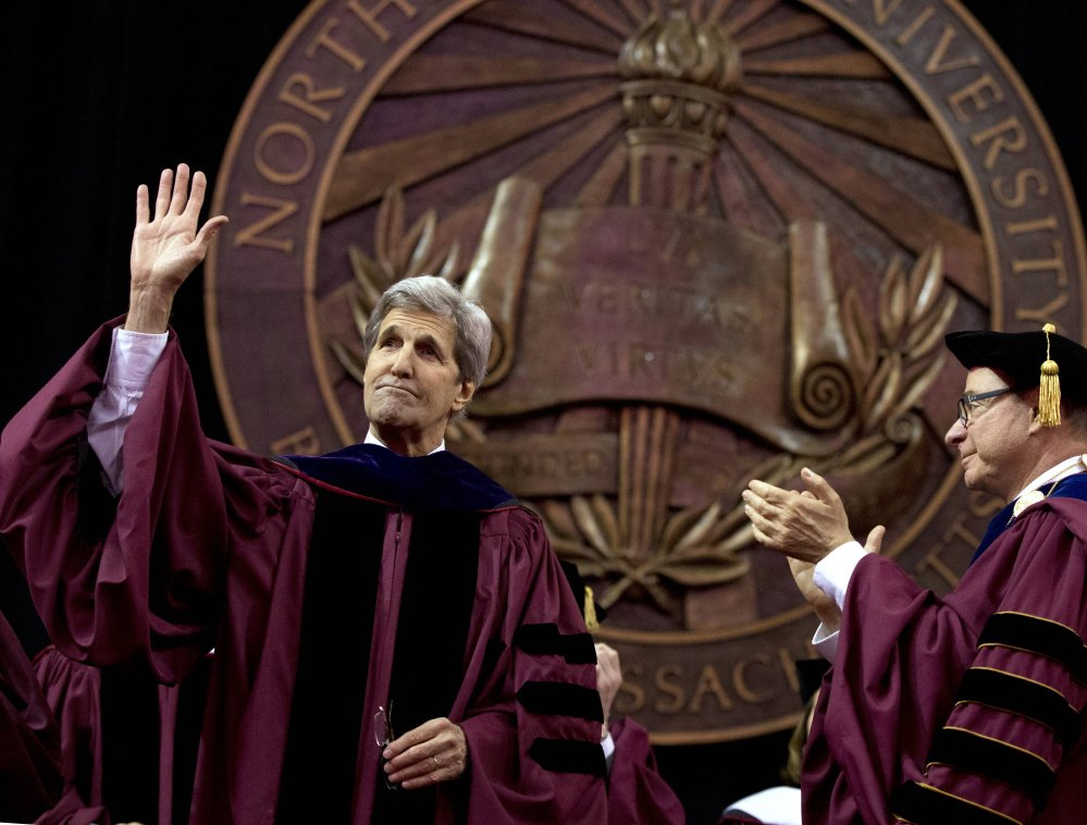 Secretary of State John Kerry acknowledges the crowd after delivering the keynote address during Northeastern University's commencement Friday as Northeastern president Joseph E. Aoun looks on.