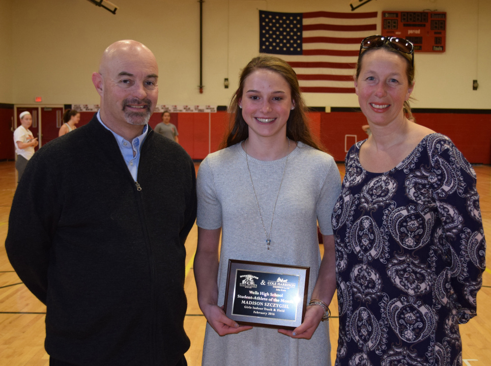 Madison Szczygiel, center, a sophomore at Wells High School, receives a plaque honoring her as Student Athlete of the Month from Jack Molloy, student activities director, and Pamela Moody-Maxon, right, of MoodyMaxon Real Estate.