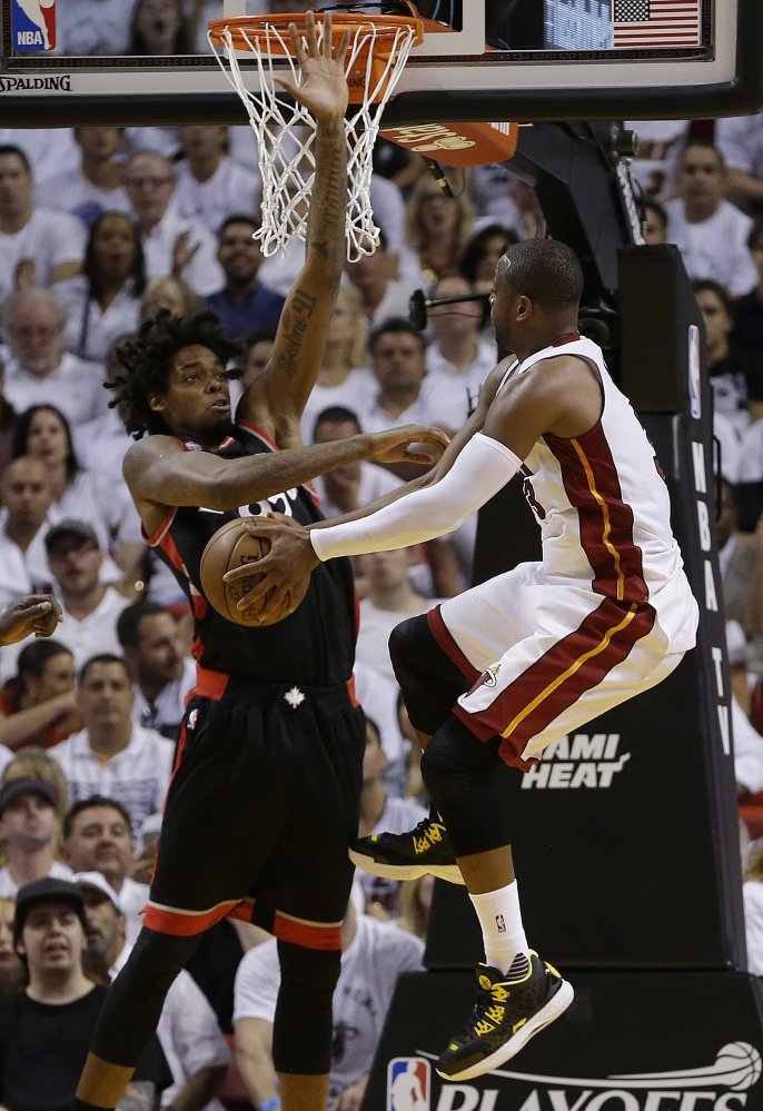 Dwyane Wade of the Miami Heat finds his way to the basket closed off by Lucas Nogueira of the Toronto Raptors during the first half Monday night. Wade carried Miami down the stretch for a 94-87 overtime victory.