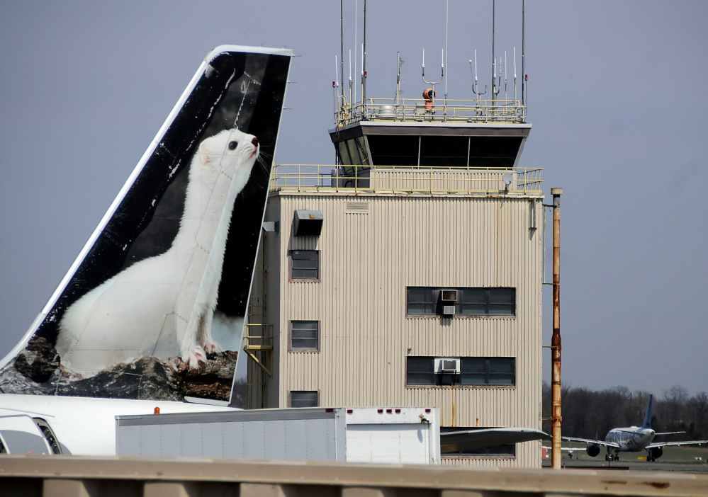 In this April 8, 2013 file photo, the painted tail appears on a Frontier Airlines aircraft parked at a gate at Trenton-Mercer Airport in Ewing, N.J.