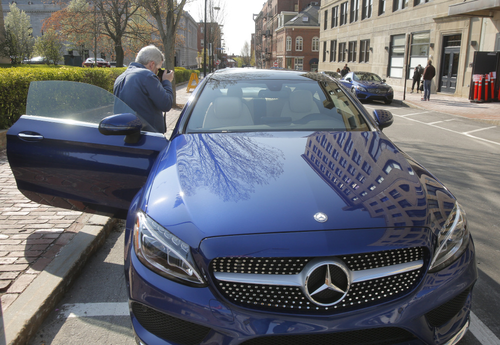 Perry Stern, editor-in-chief of Automotive Content Experience, a website that reviews automobiles and covers the auto industry, takes photos of the interior of a Mercedes C300 coupe on Market Street in Portland on Thursday.