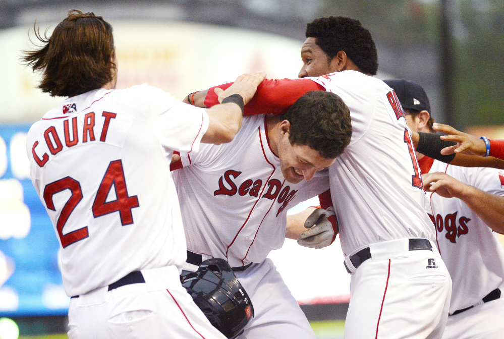 Nate Freiman, center, is swarmed by teammates after hitting a walk-off single for the Portland Sea Dogs in the opener of a doubleheader Friday night against the Binghamton Mets. The Sea Dogs won the opener 1-0.