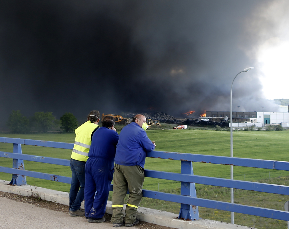 Workers watch as a cloud of thick, acrid smoke rises from a fire in Sesena, Spain, on Friday. The dump that is ablaze reportedly contains 110,000 tons of used tires.