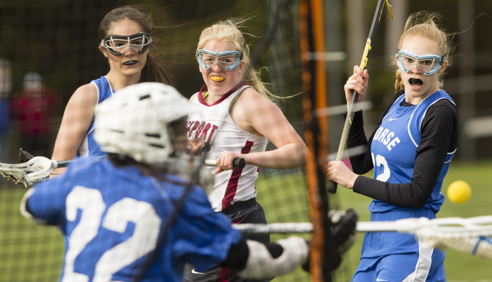 Morse goalie Zenaide McCarthy makes a save on a shot by Freeport's Lindsay Cartmell as teammates Isabella Monbouquette, left, and Mae Winglass watch in Monday's girls' lacrosse game at Freeport.