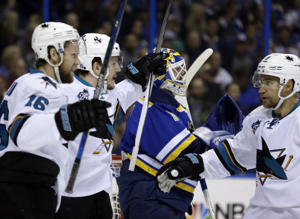 San Jose Sharks center Tommy Wingels, second from left, celebrates a goal with center Nick Spaling, left, and defenseman Justin Braun, right, during the first period of San Jose's 4-0 win over the Blues on Tuesday.