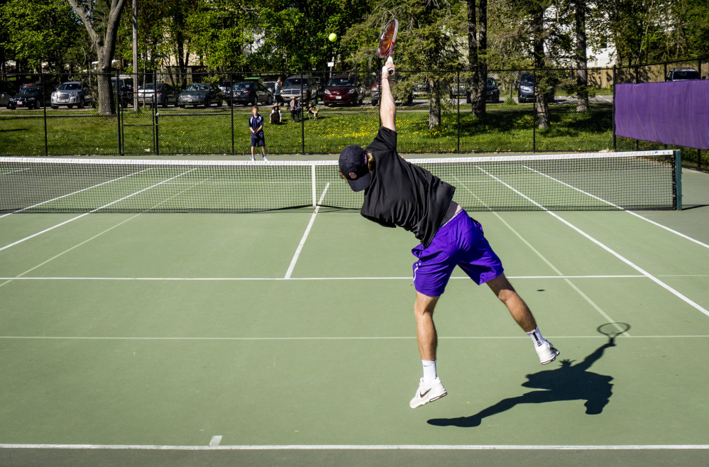 Will Weeks of Deering serves to Quinn Clarke of Portland during their boys' tennis match Wednesday at Deering High. Clarke won the match 6-3, 6-4 but Deering improved to 7-2 as a team with a 3-2 victory. Portland is 5-4.