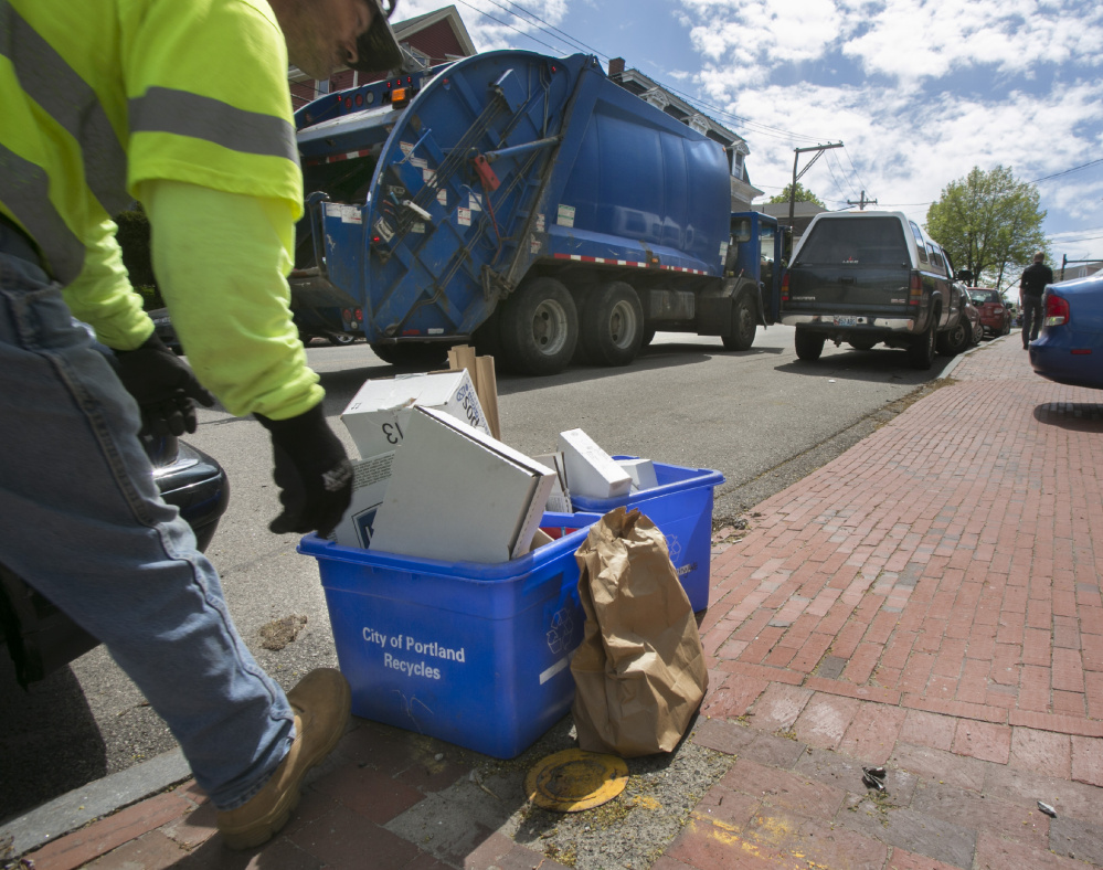 Recycling is picked up Thursday on Deering Avenue in Portland. Crews use different trucks to collect trash and recyclables and aren't allowed to mix the two, except when authorized because of unsafe road conditions.