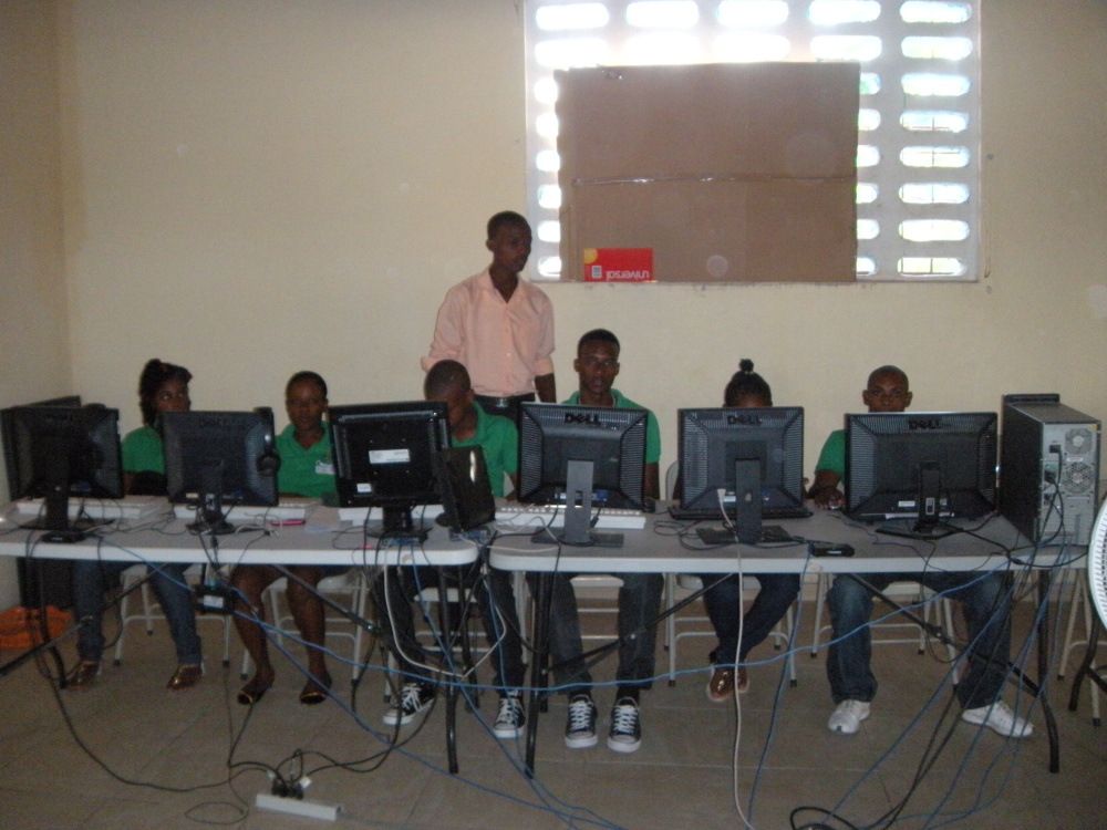 Photo courtesy of Jeanne Otis Teacher Yves-Marie Laurent works with students in the St. Patrick computer lab in January.