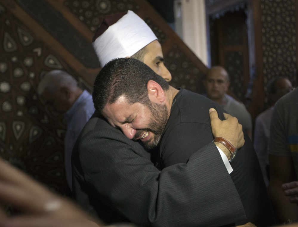 The imam of al Thawrah Mosque, Samir Abdel Bary, gives condolences to film director Osman Abu Laban, center, who lost four relatives in the EgyptAir plane crash.