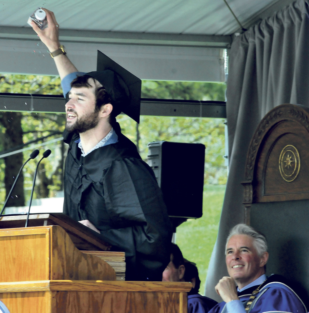 Colby College senior class speaker Brendan Leonard gestures during his address to fellow graduates at the college commencement in Waterville on Sunday. At right is college president David Greene.
