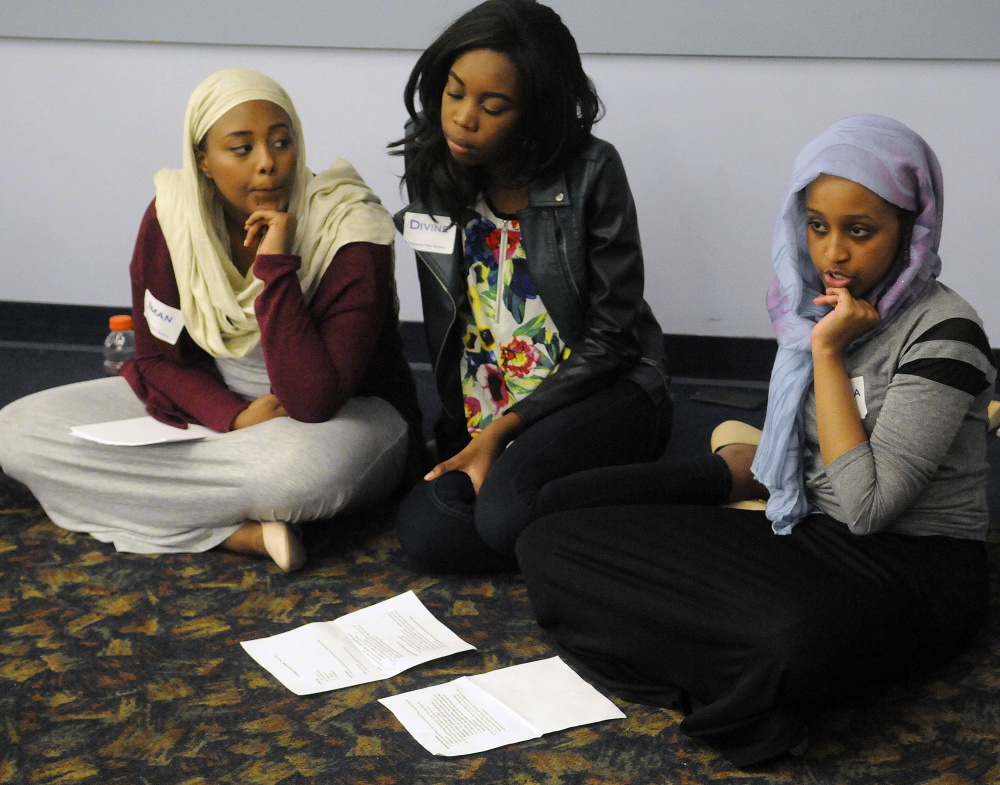 Lewiston High School students Iman Abdalla, left, Divine Selengbe and Zakiyah Sheikh moderate a discussion Monday with other civil rights team members about white privilege and stereotypes during a conference in Augusta.