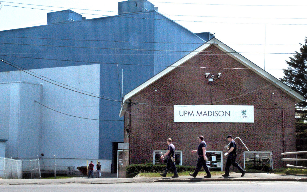 Mill workers carry tools into the Madison Paper Industries mill in Madison on Monday. The mill ended production last Saturday and will close.