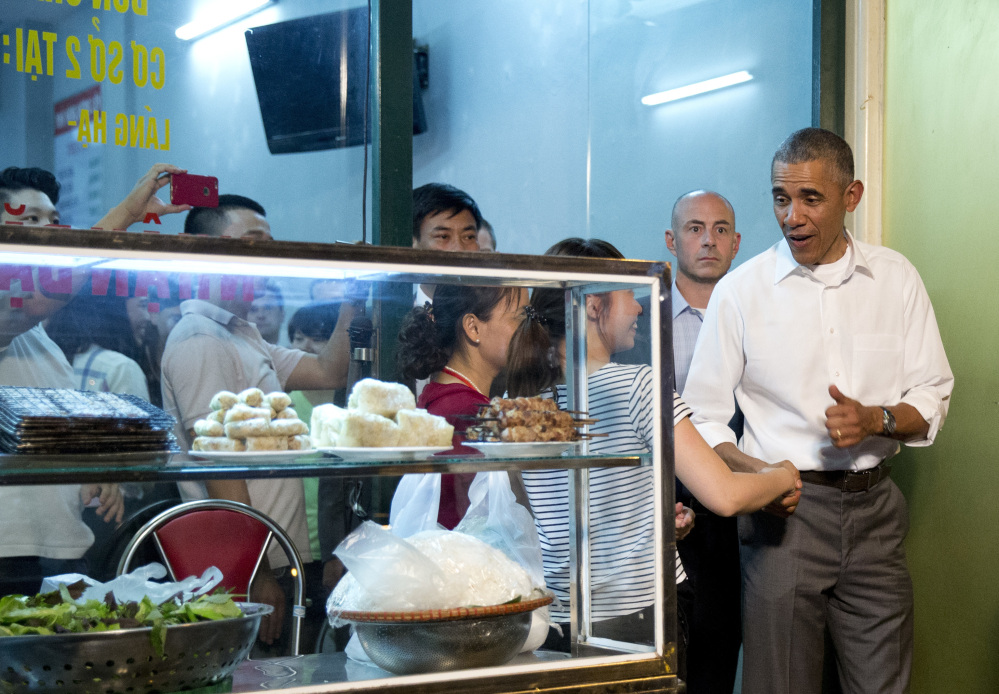 President Barack Obama greets women at the door as he walks from the Bún chả Hương Liên restaurant after having dinner with American Chef Anthony Bourdain in Hanoi, Vietnam, Monday, May 23, 2016. (AP Photo/Carolyn Kaster)