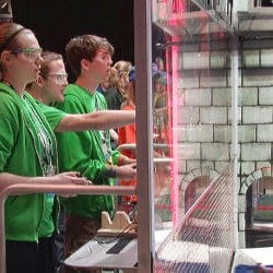 """Bonny Eagle High School BERT Robotics Team members Amber Lindberg, left, Jacob Moss and George Mitchell guide their robot """"Stein"""" during the FIRST Robotics Championship in St. Louis."""