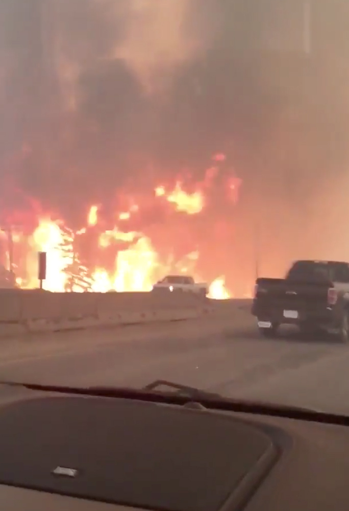 This photo provided by Tyler Burgett shows flames from a wildfire along Highway 63 in Fort McMurray, Alberta, Tuesday.