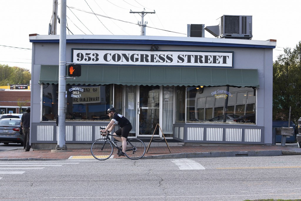 A cyclist passes 953 Congress Street which will soon reopen as Salty Sally's Bar & Grille.