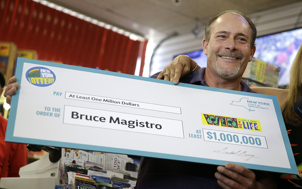 Bruce Magistro holds up a facsimile check while talking to reporters about winning $1 million in the New York Lottery for a second time. The Associated Press
