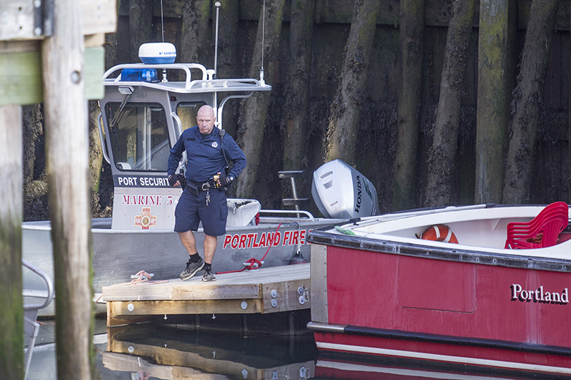 A police officer by the Casco Bay Ferry Terminal where police had put crime scene tape up around the area where the Portland Fire Department's boat is docked.