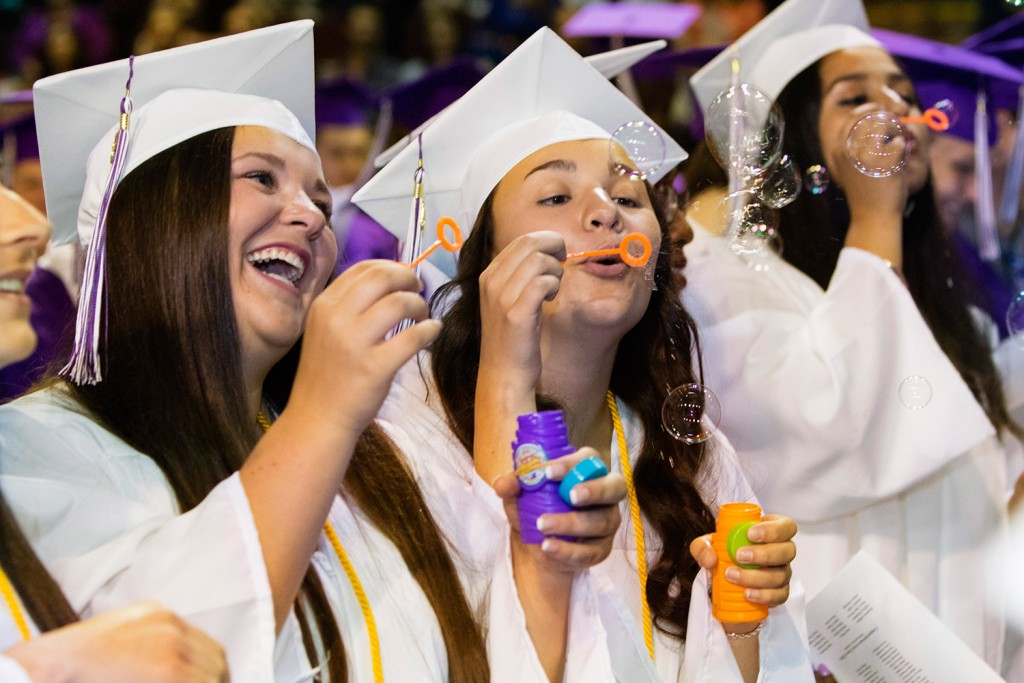 Deering High School seniors Cassidy Coyne, Sofia deOliveiro and Neilah Habibzai blow bubbles during their graduation Thursday at the Cross Insurance Arena in Portland.