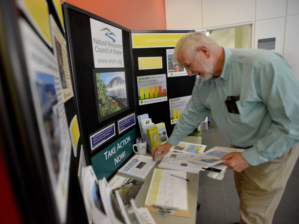 David Woodsome, state senator from Sanford, picks up pieces of solar power literature before speaking Thursday at The Future of Solar in Maine Forum at Colby College in Waterville.