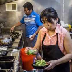 Siwaporn Roberts plates a takeout dish as her son, Ben Boonseng, finishes an appetizer on the grill in the kitchen of Thai Essan on Forest Avenue in Portland, the restaurant they own together.
