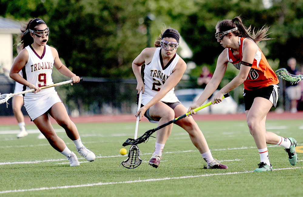 Addy Paradis, left, of Thornton Academy, looks on as teammate Rachel Richard, center, fights for the ball with Biddeford's Taylor Turgen during a Class A South girls lacrosse quarterfinal on Wednesday in Saco. Thornton won the game, 15-1.