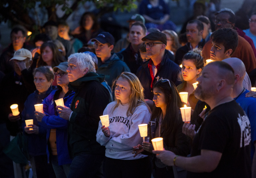 Part of the large crowd listens to speakers Monday during a candlelight vigil outside Portland City Hall, one of numerous vigils held around the state.