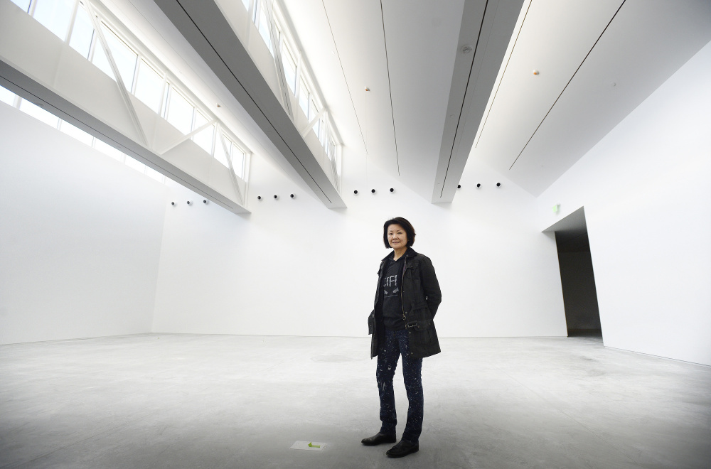 New York architect Toshiko Mori, who has a home on North Haven, poses inside the main gallery of the new Center for Maine Contemporary Art in Rockland. She has enclosed the museum in glass, allowing as much light to enter as possible. A saw-toothed roof filters light into the spacious galleries from above.