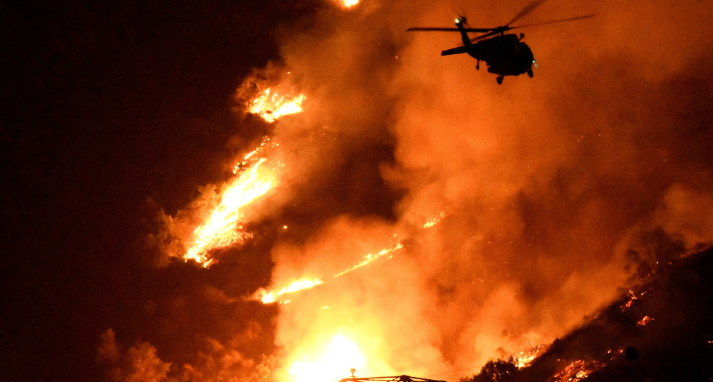 A Los Angeles County fire helicopter makes a nighttime water drop to slow the advance of a giant fire in the San Gabriel Mountains of Southern California on Monday. The wind had started to bring the fire down the mountains closer to homes.