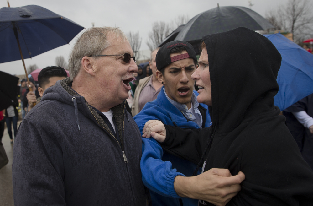this Sunday, March 13, 2016 file photo, a supporter of Republican presidential candidate Donald Trump, left, and a protester argue before the candidate's arrival ahead of a campaign stop at the Savannah Center in West Chester, Ohio. Democratic and Republican views of the opposing political party have sunk to such lows that many say their rivals make them feel afraid, according to an opinion poll released by the Pew Research Center on Wednesday, June 22, 2016.