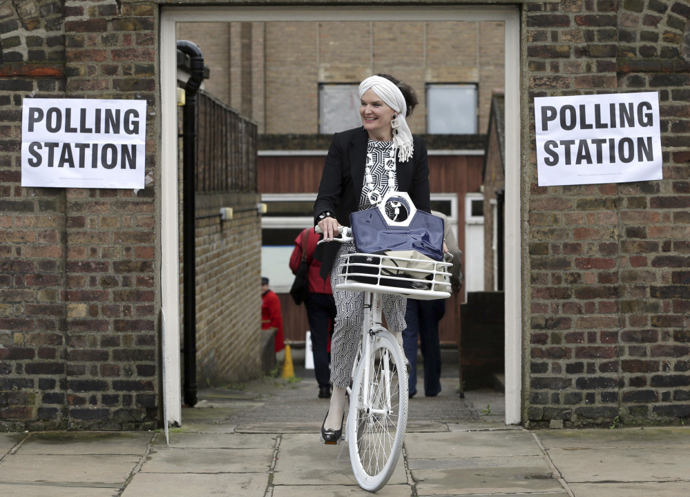 A woman on a bicycle leaves a polling station near to the Royal Chelsea Hospital in London on Thursday. Voters in Britain are deciding Thursday whether the country should remain in the European Union.