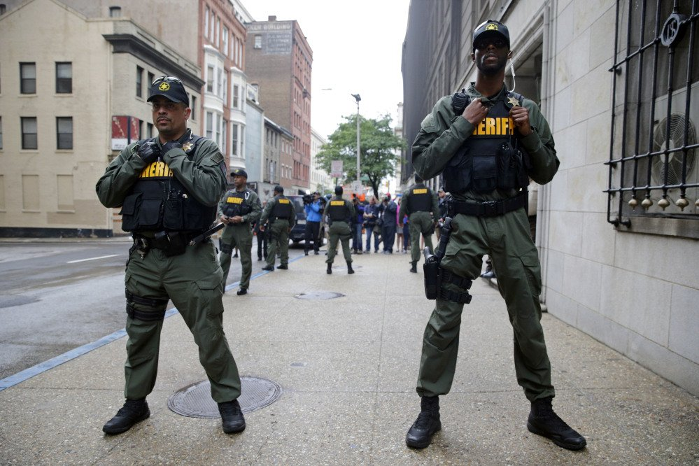 Members of the Baltimore City Sheriff''s Office stand guard outside a courthouse as they await the arrival of Officer Caesar Goodson, one of six Baltimore city police officers charged in connection to the death of Freddie Gray. y