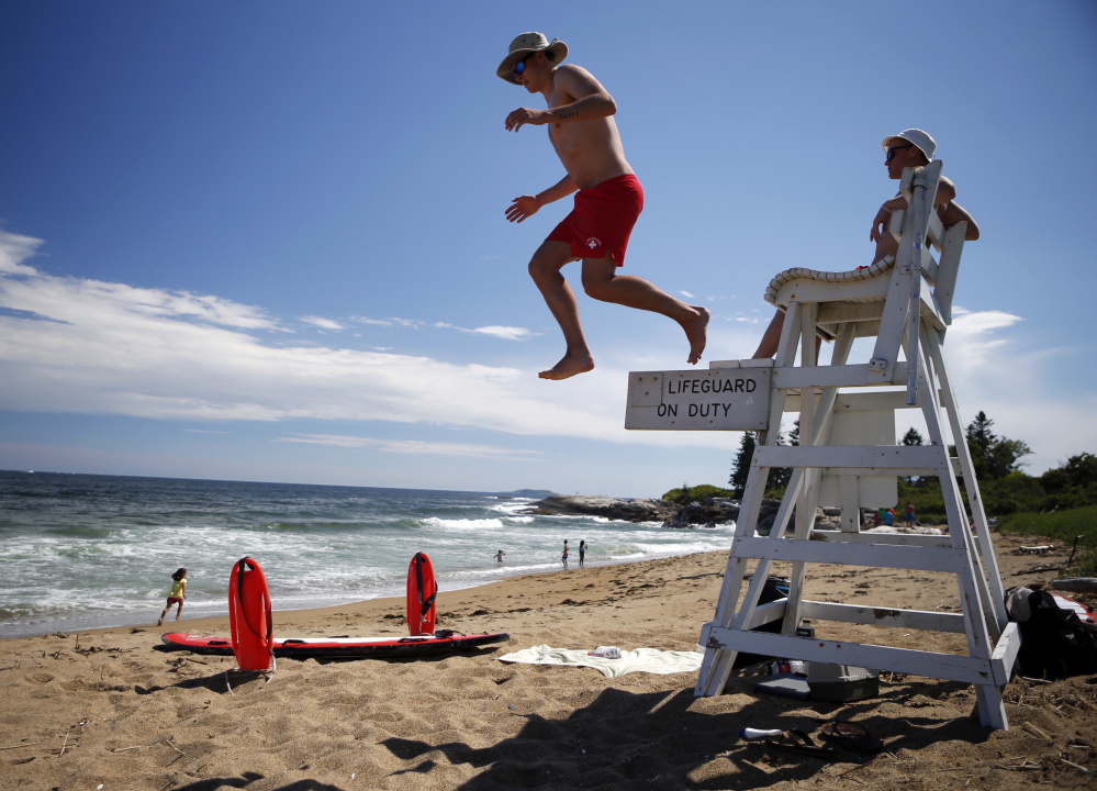 Lifeguards Nate Samson, 18, of Brunswick, Maine, left, and Kyle Hummel, 19, of Bath, Maine, patrol a section of Mile Beach on Thursday at Reid State Park in Georgetown. States where lifeguarding is seasonal have a harder time keeping positions filled.