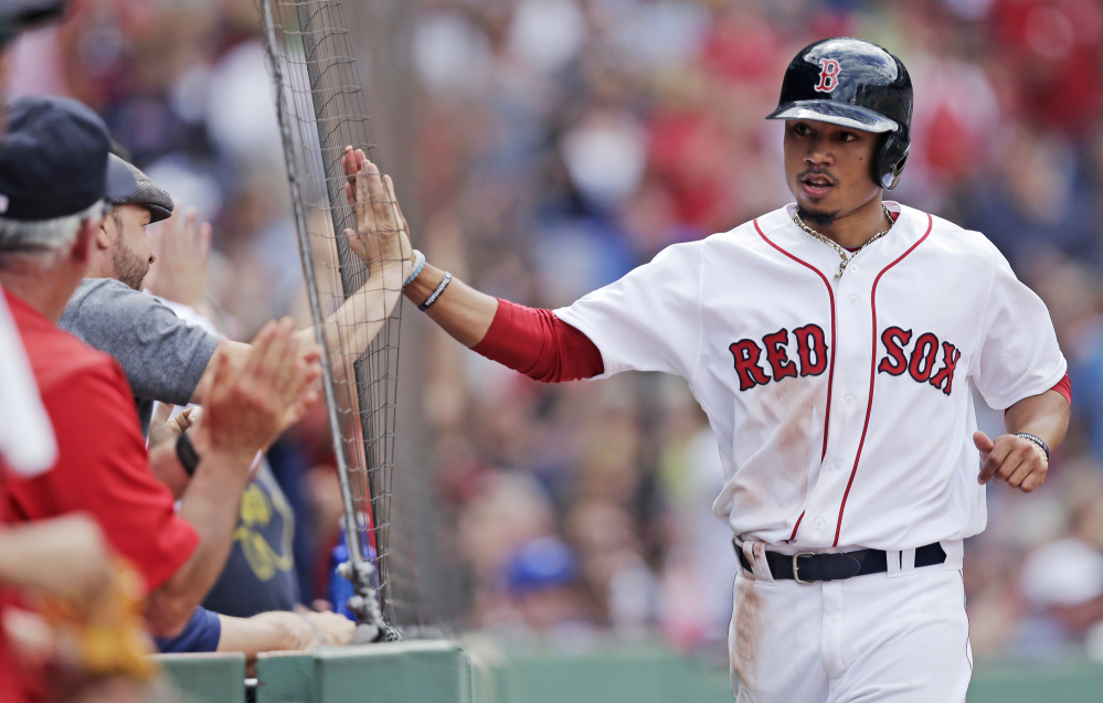 Boston's Mookie Betts, right, high-fives actor Donnie Wahlberg after scoring on a double by Dustin Pedroia in the fifth inning at Fenway Park on Thursday. Boston won the game in 10 innings, 8-7.