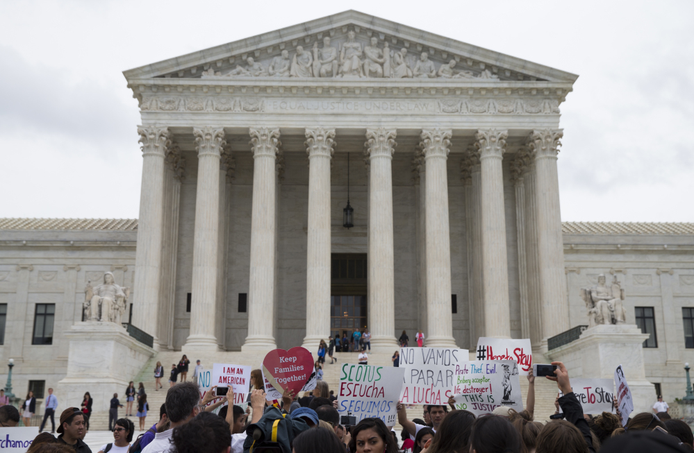 Demonstrators gather outside the Supreme Court in Washington on Thursday. A divided court upheld the University of Texas admissions program that takes account of race.