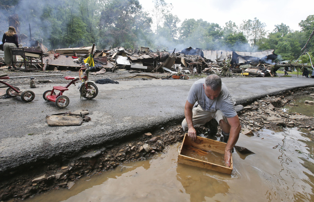Mark Lester cleans out a box with creek water as he cleans up from severe flooding in White Sulphur Springs, W.Va., on Friday.
