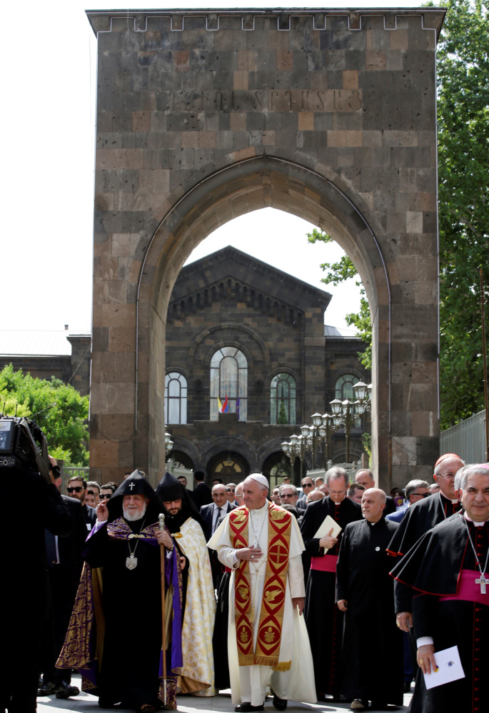 Pope Francis, center, and Catholicos of All Armenians Karekin II, left, arrive at the Apostolic Cathedral in Etchmiadzin, Armenia, on Friday. The visit marks the centenary of a massacre.
