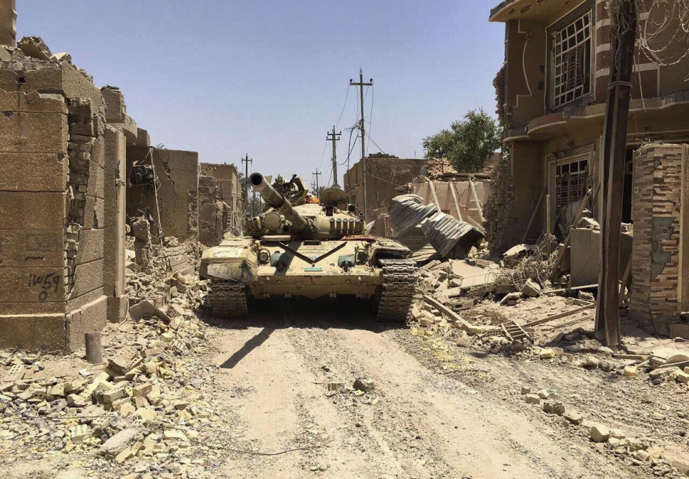 Iraqi security forces move through the Al-Julan neighborhood after defeating Islamic State militants in Fallujah, Iraq, on Sunday.