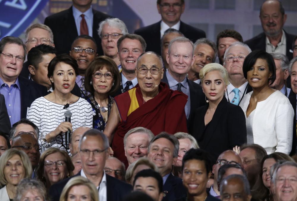 The Dalai Lama and Lady Gaga, center second from right, pose for a photo with mayors attending the U.S. Conference of Mayors in Indianapolis, Sunday, June 26, 2016.