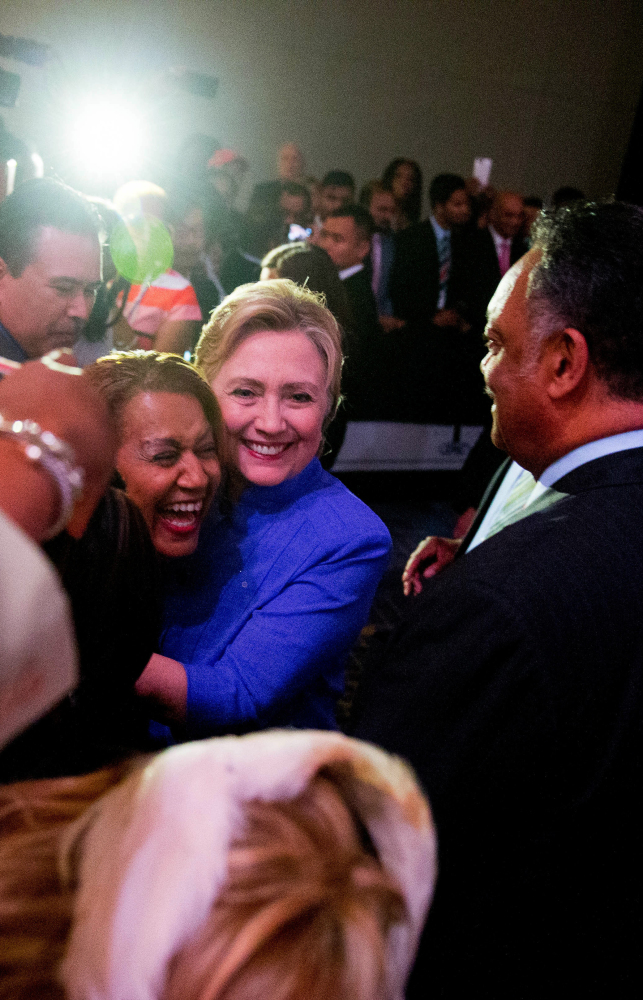 Rev. Jessie Jackson watches as Hillary Clinton hugs a member of the audience after speaking at a Rainbow PUSH Women's International Luncheon on Monday.