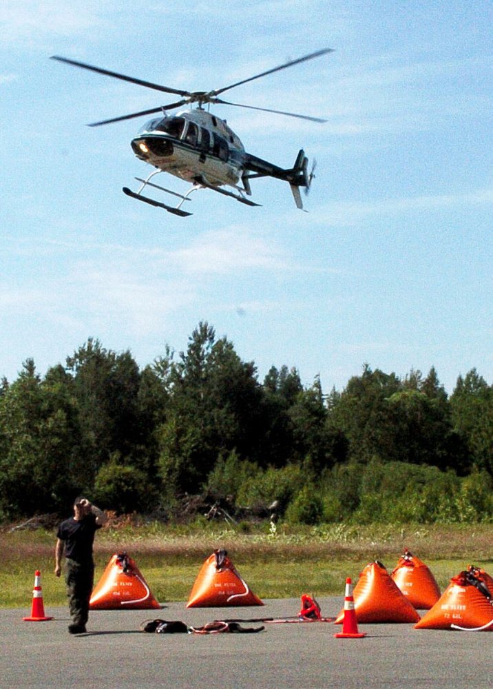 A Maine Forest Service helicopter lands at a command center at the Kingfield Fire Department as firefighters from the service and area departments battle a lightning-sparked fire on nearby Mount Abraham on Monday. The orange containers on the ground are portable tanks of water brought to the top of the mountain for firefighters.