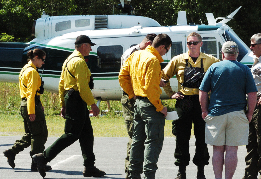 Maine Forest Service personnel consult at the Kingfield Fire Department on the status of the eight firefighters battling a fire on top of nearby Mount Abraham on Monday, with incident commander Shane Nichols, third from right, and Maine Forest Service Chief Ranger William Hamilton, right. Hamilton said the terrain and heat have been brutal for firefighters.