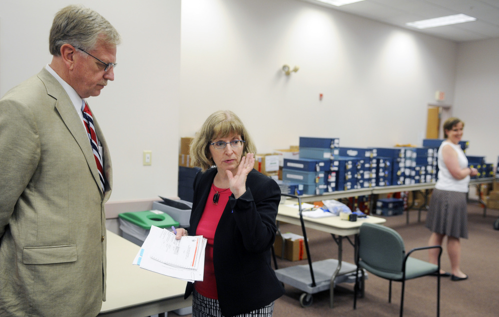Candidate Mark Holbrook speaks with Deputy Secretary of State Julie Flynn on Tuesday before the beginning of the 1st Congressional District primary race recount in Augusta.