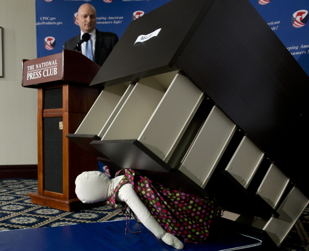 During a news conference in Washington, D.C., on Tuesday, Consumer Product Safety Commission Chairman Elliot Kaye watches how an Ikea dresser can tip and fall on a child.