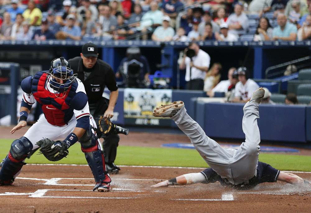 Jason Kipnis of the Indians scores face first ahead of the throw to Braves catcher A.J. Pierzynski on a Jose Ramirez hit in the first inning Tuesday night in Atlanta.