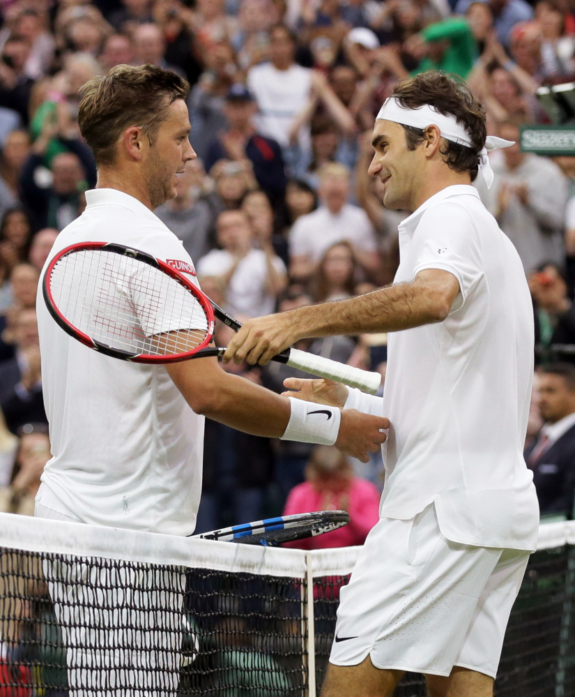 Roger Federer shakes hands with Marcus Willis, left, after beating him in their men's singles match on day three of Wimbledon in London on Wednesday.