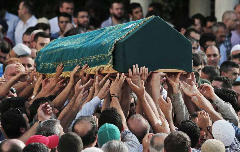 Mourners in Istanbul on Wednesday carry the coffin of Muhammed Eymen Demirci, 25, who was killed Tuesday at Istanbul's Ataturk Airport.