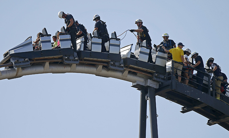 Oklahoma City firefighters rescue amusement park goers stuck on a stalled roller coaster at Frontier City in Oklahoma City on Wednesday, June 29, 2016. (Bryan Terry/The Oklahoman via AP)