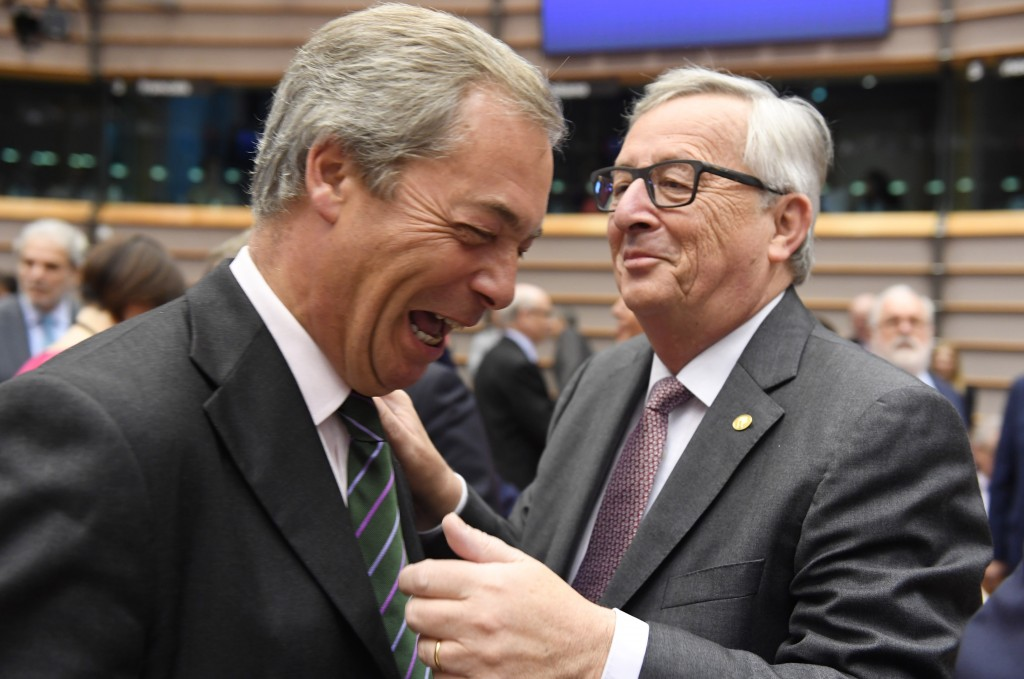 European Commission President Jean-Claude Juncker, right, greets UK Independent Party leader Nigel Farage during a special session of European Parliament in Brussels on Tuesday. EU heads of state and government are meeting Tuesday and Wednesday in Brussels for the first time since Britain voted to leave the European Union. Associated Press