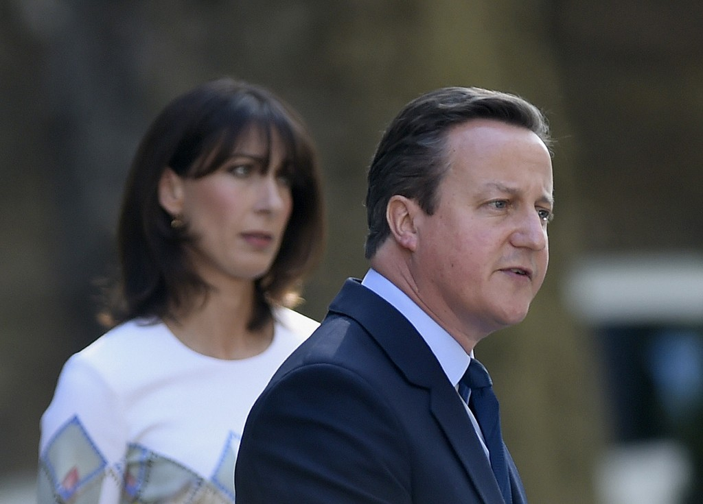 Britain's Prime Minister David Cameron speaks outside 10 Downing Street Friday as his wife Samantha looks on. Cameron says he will resign by the time a party conference takes place in the fall. PA via AP